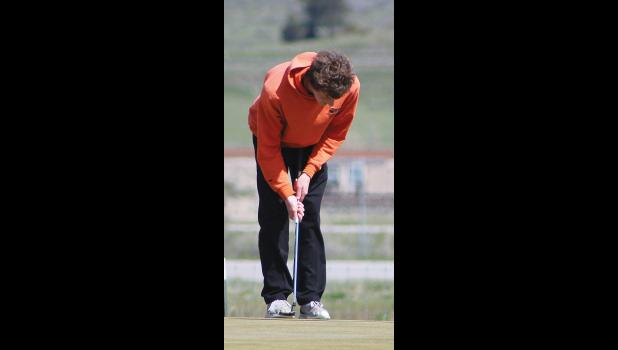 An Absarokee golfer makes his putt on the 9th hole.