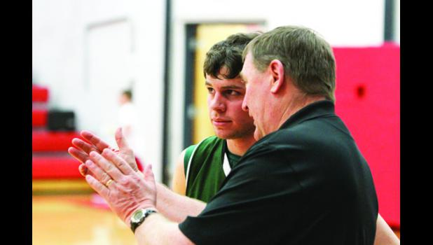 Columbus head coach Paul Barta confers with Cougar senior Kiefer McKay during the game in Three Forks.