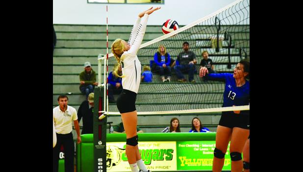 Columbus Cougar Brenna Rouane blocks the ball against Big Timber.