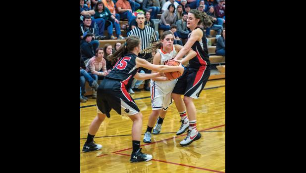 Husky senior Maisey Sheppard is trapped by Panther juniors MacKinzie Verke, left, and Tehya Ray.