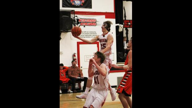 Park City junior Connor McNeil goes up to put the ball in the basket against Absarokee.