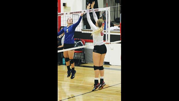 Alyx Grabowska reaches up to block a ball hit by a Roberts player.