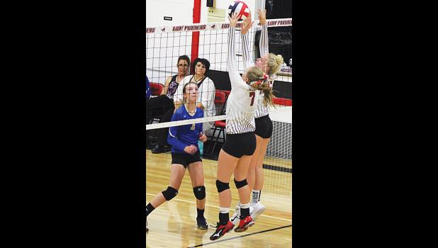 Andee Baker (left) and Blakely Verke jump to block the ball during Saturday's game against Roberts.