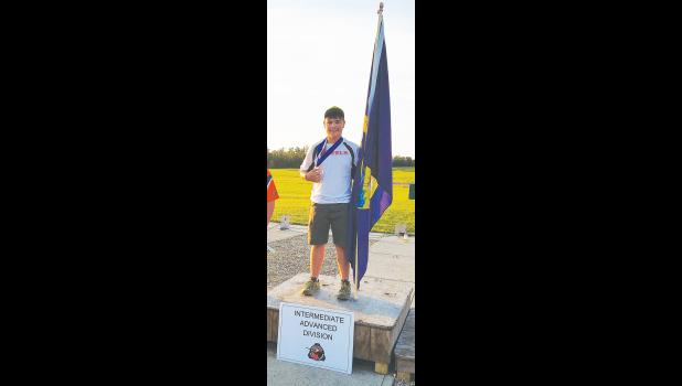 Preston Bailey displays the medal he earned in skeet.