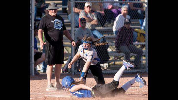 Renegade Erin Campbell was safe diving back to first base against Lewistown on April 8. Renegade head coach John Smith, left, watches the action.