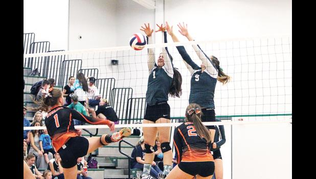 Columbus Cougar sophomore Morgan Kirch and junior Maddi Carman block a hit by Husky senior Erin Campbell on Sept. 27.