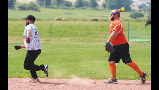 Shortstop Adam Emmett, of Emmett's, chases Cole Waltner, of Compass, into an out at third base.