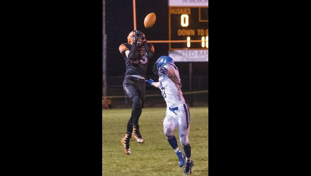 Husky wide receiver Kyle Kirby catches a pass over the head of a Lone Peak player.
