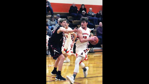 Right: Absarokee senior Roman Zugaza charges the basket for a shot last Thursday.  He led the team with 12 points.