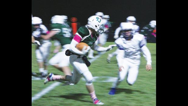 Cougar running back Kenneth Smith speeds past the Trojan defenders on his senior night.