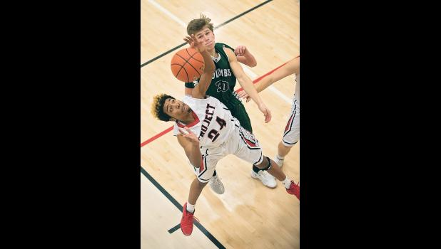 Cougar Gabe Brocklebank looks on as a Huntley player reaches for a rebound.