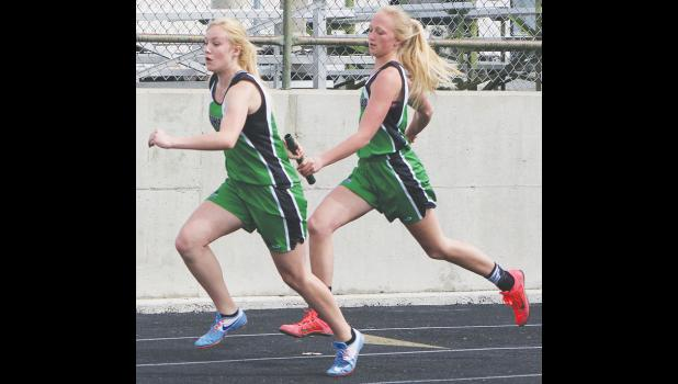 Columbus 400 relay team members (from left) RaiLeigh Strommen and Brenna Rouane make an exchange on Friday.