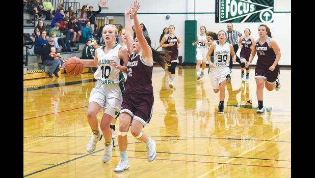 Cougar Brenna Rouane slows down the pace after bringing the ball down the court against Roundup.