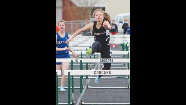 A Park City trackster flies over a hurdle during the Absarokee Invite.