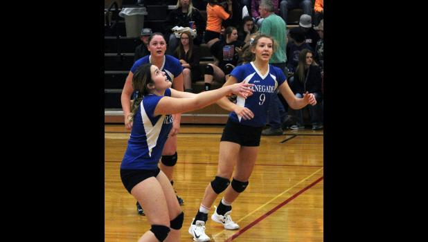 Senior Renegade Nynah Bryant sets up a play as Destiny Ayers (left) and Carlee Blodgett (right) look on.