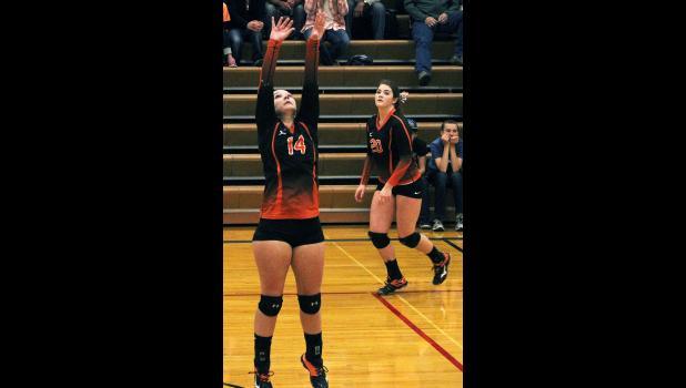 Husky senior Caitlin Young sets the ball back to Rebecka Lester.