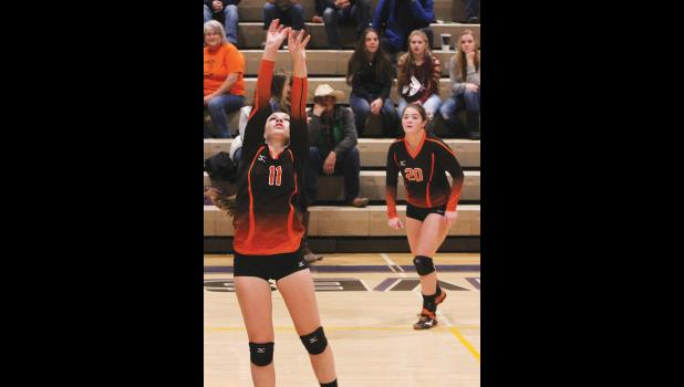 Absarokee sophomore Kaiya Holmquist (left) sets the ball as  Lester waits for the play.