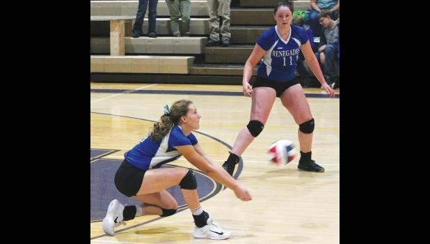 Renegade sophomore Carlee Blodgett digs the ball as senior Destiny Ayers looks on.