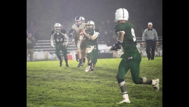 Columbus Quarterback Eddie Foos looks for tight end Tommy Campbell (far right) through the mist on Friday.