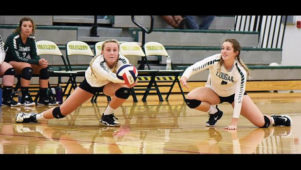 Camryn Ault digs the ball as Madi Carmen is ready to assist.