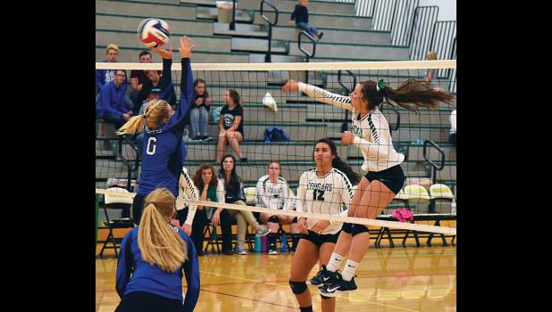 Columbus Cougar Morgan Kirch slams the ball over the net on Thursday.