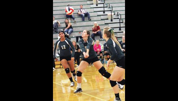 Columbus junior Camryn Ault prepares to bump the ball while junior McCamey Miller watches. Above, junior Maddi Carman passes the ball while junior Uluwehi Brooks, left, and junior Shelby Wolery, right, wait for the ball.
