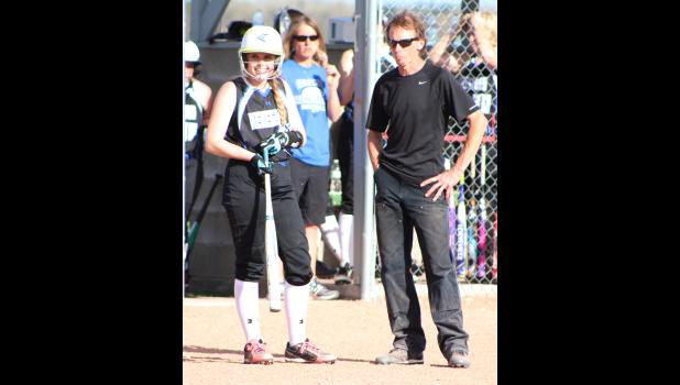 Arica Hedges talks with Coach Randy Crawford as the Colstrip Fillies take a timeout to talk with their pitcher.