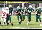 Columbus Cougar senior Connor Solomon breaks through the open hole led by senior blockers Cody Wegner (69) and EJ Daniels (11) at the Sept. 16 Homecoming game against Three Forks.