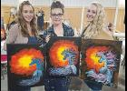 Three ladies show off their final products at the Fishtail Sip and Paint last Saturday.